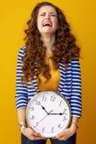 Donna alla moda triste isolata su fondo giallo con l'orologio Immagine Stock Libera da Diritti