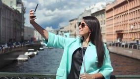 Donna alla moda turistica sorridente che prende selfie facendo uso della condizione dello smartphone sul ponte sopra il fiume video d archivio
