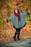 Donna alla moda in una tunica nel parco di autunno Immagine Stock