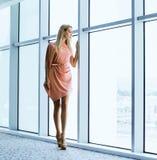donna alla moda vicino alla finestra nell'edificio per uffici fotografia stock