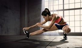 Donna alla palestra che fa allungando gli esercizi e sorridendo sul pavimento Immagine Stock