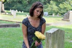 Donna alla pietra grave con i fiori gialli fotografia stock