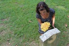 Donna alla pietra grave con i fiori gialli fotografia stock libera da diritti