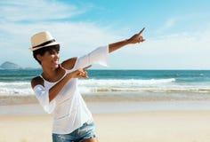 Donna alla spiaggia che indica ugualmente lo spazio della copia per la promozione Fotografia Stock
