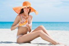 Donna alla spiaggia con idratante Fotografia Stock Libera da Diritti