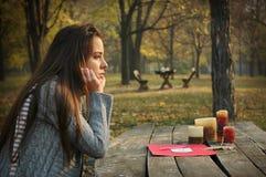Donna alla tavola nel parco di autunno con carta e le candele Immagine Stock