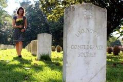 Donna alla tomba del ` s del soldato sconosciuto con i fiori gialli immagine stock