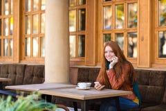 Donna allegra attraente che si siede con il cellulare in caffè all'aperto Immagine Stock