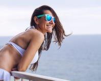 Donna allegra in bikini ed occhiali da sole sul mare Fotografie Stock