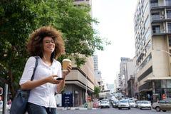 Donna allegra che cammina nella città con il telefono cellulare Immagini Stock