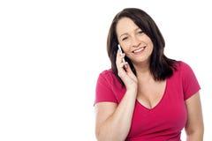 Donna allegra che comunica sul telefono Fotografia Stock