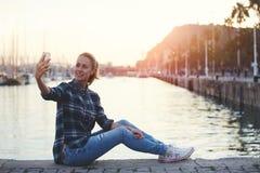 Donna allegra che fa autoritratto sulla macchina fotografica dello Smart Phone mentre riposando dopo la camminata fuori Immagine Stock Libera da Diritti