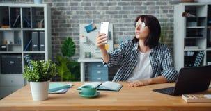 Donna allegra che fa video chiamata online con lo smartphone nella stanza dell'ufficio archivi video