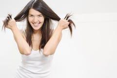 Donna allegra che gioca con i suoi capelli Immagini Stock