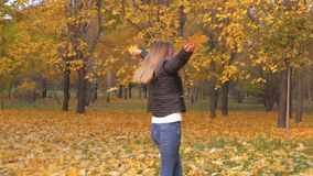 Donna allegra che gira intorno nelle foglie di Autumn Park Holding Golden Yellow stock footage