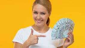 Donna allegra che indica dito al mazzo di dollari, condizioni di credito proficue stock footage