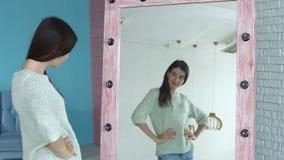 Donna allegra che la esamina riflessione in specchio archivi video