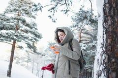 Donna allegra che manda un sms sullo smartphone arancio durante il viaggio alla foresta nel modello castana di inverno che indoss Immagine Stock Libera da Diritti