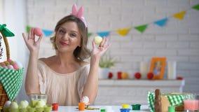 Donna allegra che mette le uova di Pasqua agli occhi divertendosi e godendo del fest luminoso video d archivio