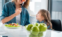Donna allegra che mostra al suo bambino come mangiare le verdure fotografia stock