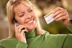Donna allegra che per mezzo del suo telefono con la carta di credito Fotografie Stock