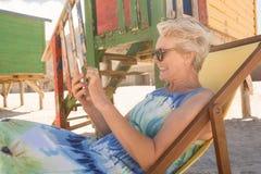 Donna allegra che per mezzo del telefono cellulare mentre sedendosi sulla sedia Fotografia Stock