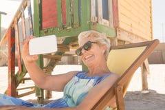 Donna allegra che per mezzo dello Smart Phone mentre sedendosi sulla sedia Immagini Stock