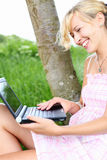 Donna allegra che per mezzo di un computer portatile all'aperto Immagine Stock