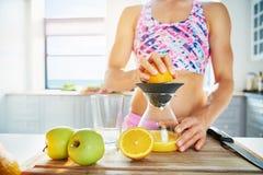 Donna allegra che preme succo d'arancia con lo spremitoio immagini stock