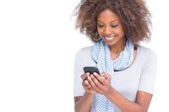 Donna allegra che scrive un messaggio di testo a macchina sul suo smartphone Fotografia Stock
