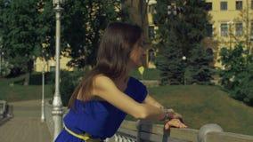 Donna allegra che si appoggia il bannister del ponte video d archivio