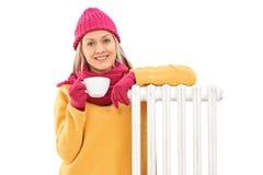 Donna allegra che si appoggia un radiatore e che tiene una tazza Immagine Stock Libera da Diritti