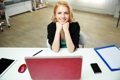 Donna allegra che si siede al suo posto di lavoro Immagine Stock