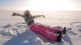 Donna allegra che si siede in inverno del campo, neve dei tiri al suo e fiocchi di neve di caduta Immagini Stock Libere da Diritti
