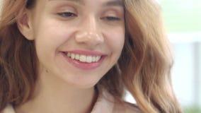 Donna allegra che sorride e che guarda per affrontare specchio in bagno domestico stock footage