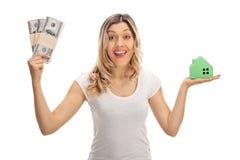 Donna allegra che tiene i pacchi di soldi e di una casa di modello Immagine Stock Libera da Diritti