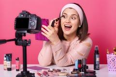 Donna allegra con l'ampia bocca aperta ed occhi che fanno esercitazione per i suoi abbonati, tenendo specchio rosa, applicando ma fotografia stock libera da diritti