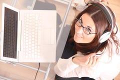 Donna allegra con un computer portatile e le cuffie Immagini Stock Libere da Diritti