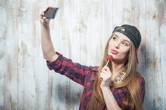 Donna allegra dei pantaloni a vita bassa con il cappello e la caramella Fotografia Stock
