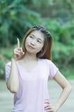 Donna allegra dell'Asia che pensa e che cerca con l'alta aspirazione Fotografia Stock