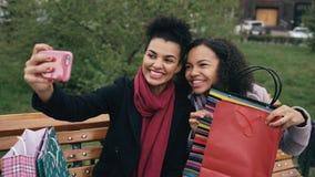 Donna allegra della corsa mista due con i sacchetti della spesa che parla alla video chiamata con lo smartpone Le ragazze che si  fotografie stock libere da diritti