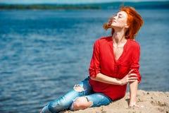 Donna allegra della testarossa che passa rapidamente i suoi capelli nell'aria Fotografie Stock