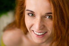 Donna allegra della testarossa con le lentiggini che ride della macchina fotografica fotografia stock