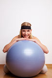 Donna allegra dietro la sfera di ginnastica Fotografie Stock Libere da Diritti