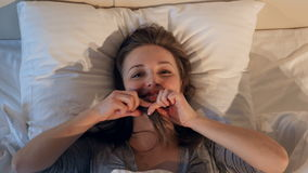 Donna allegra e felice che fa i fronti a letto 4K archivi video