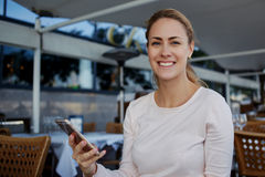 Donna allegra felice che sorride alla macchina fotografica mentre telefono delle cellule di uso durante la prima colazione in caf Fotografia Stock Libera da Diritti