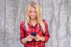 Donna allegra felice sorridente con capelli biondi, in camicia a quadretti facendo uso del cellulare 3g, 4g interent per la chiac Fotografia Stock