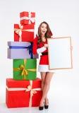 Donna allegra in panno del Babbo Natale che tiene bordo in bianco Fotografie Stock