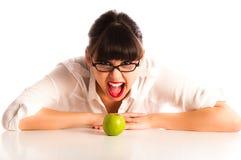 Donna allo scrittorio con i vetri da portare della mela verde Immagini Stock