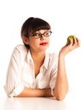 Donna allo scrittorio con i vetri da portare della mela verde Fotografia Stock Libera da Diritti